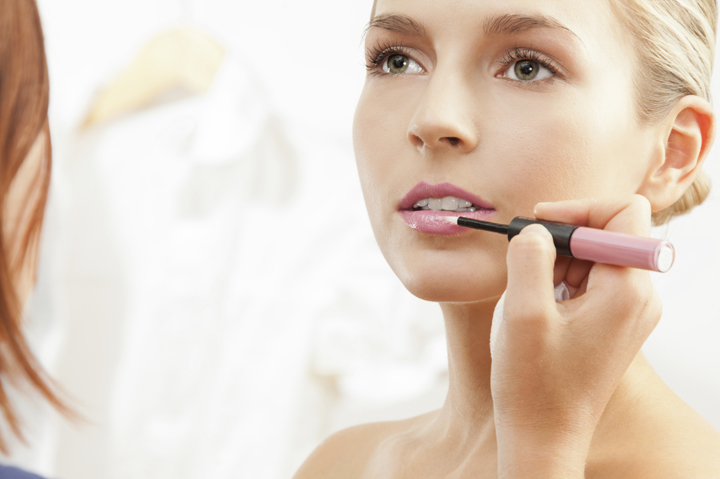Makeup artist apply pink lipglass on the lips of a model