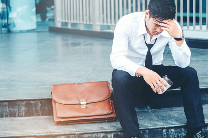Tired or stressed businessman sitting on the walkway after work Stressed businessman concept