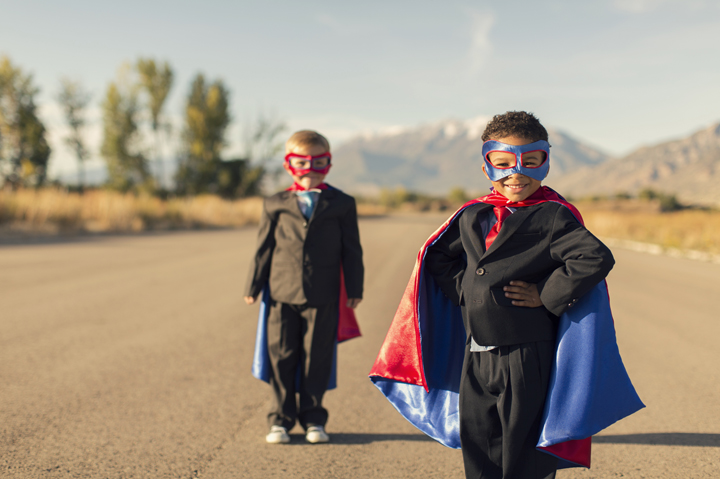 Two business boys are dressed in superhero capes and masks while standing on a road in Utah, USA. They form powerful business partnership and team.